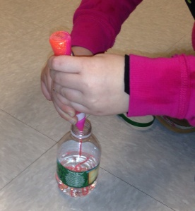 Fill a plastic water bottle 1/3 of the way full. Add 1-2 squirts of glitter glue into the bottle (to make this festive, we used a mix of pink and orange). Shake vigorously with 2 hands until the glitter glue is dissolved and you do not see any more clumps. This portion of the activity is great for bilateral upper extremity strengthening, and postural control/stability.